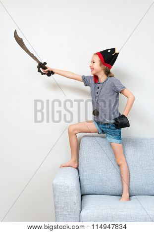 Pirate Little Girl Playing On Sofa At Home.