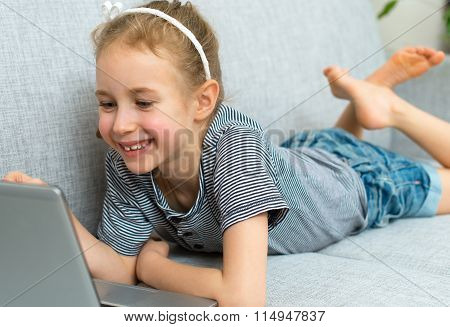 Smiling Little Girl On The Sofa With Laptop.