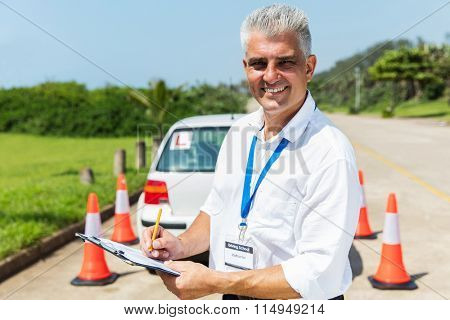 handsome senior driving instructor writing on clipboard