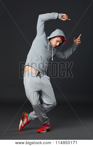 Fullbody Portrait Of Young Cool Man Dancing On Dark Background.