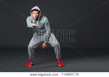 Full body Portrait Of Young Cool Man Dancing On Dark Background.