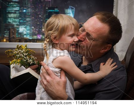 Father embraces and kisses the daughter.