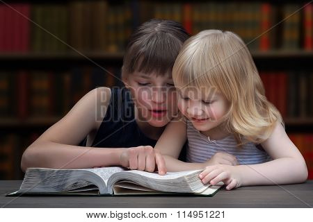 Children reading a book in the library.