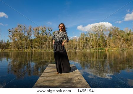 Woman Standing On A Wooden Bridge