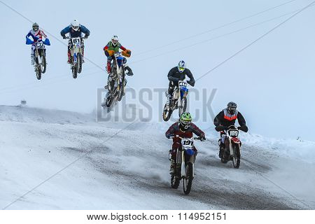 group motorcycle racer riding on snow-covered mountain after start