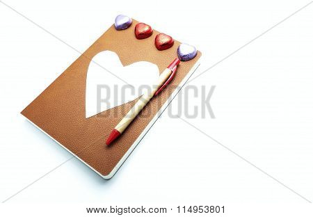Leather brown book and wooden pen with heart chocolates and white heart paper and eyeglasses case