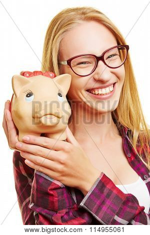 Smiling young woman holding piggy bank in her hands