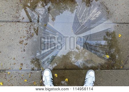 Cityscape reflection in path puddle