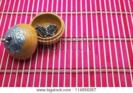 Metal roses in opened wooden circle box with silver design on cover, on pink bamboo mat/pad