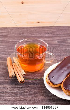 Tea with cinnamon and cakes eclairs