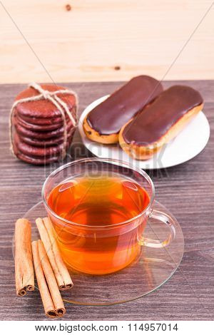 Tea with cinnamon and cakes eclairs on