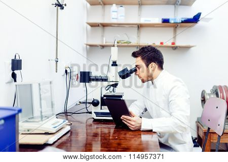 Pharmacist And Medical Scientist Looking At Tablet And Comparing Microscope Results From Sample Expe