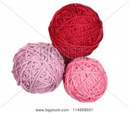 Three Skeins In Pink And Red Tones Over White