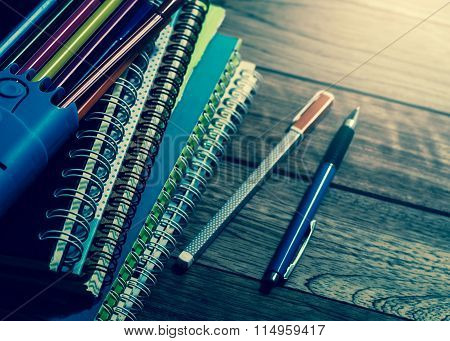 Heap Of Notebook With Pens On Wooden Table