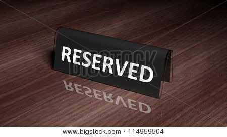 Black glossy reservation sign on wooden surface with reflection