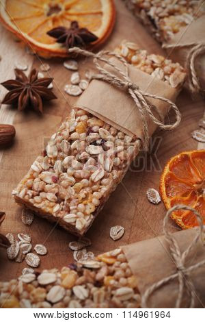 Granola bars with cereals and dried fruit on wooden table