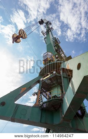 Big Industrial Port Crane In Front Of Blue Sky With White Clouds