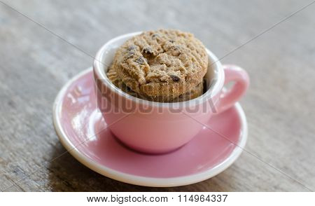 Cookies In Pink Cup On Wooden Table
