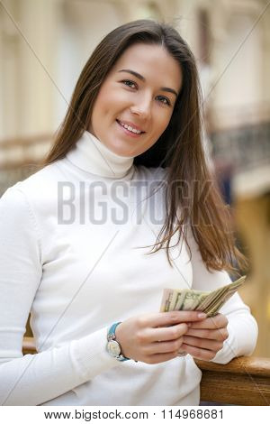 Brunette female holding and showing dollars with happy face and toothy smile while looking at camera