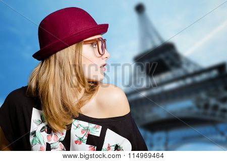 Charming girl in hipster glasses on Eiffel tower blurred background