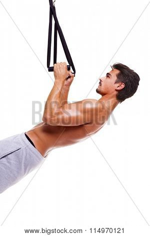 Fit man doing push ups training arms with fitness straps, isolated over white background