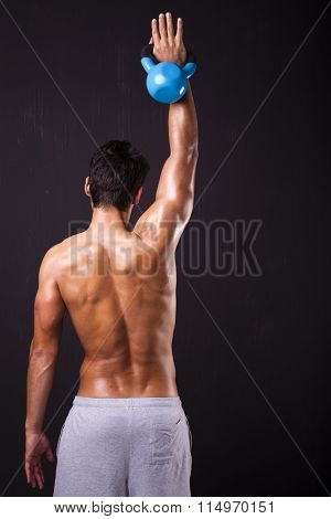 Back view of young fit man exercising the shoulders