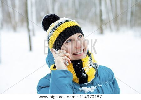 Calling by phone women. Portrait of a beautiful young woman in a turquoise feather bed and a knitted cap on a background of a winter park