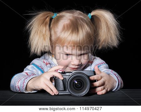 Little girl photographs. The child holds the camera