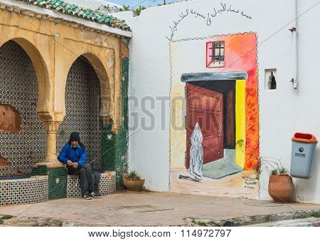 One Moroccan Old Man Sit Near The Colourful Painting