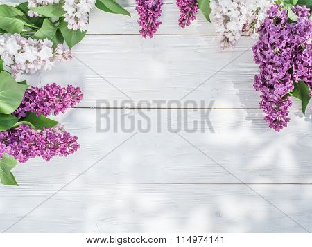 Blooming lilac flowers on the old wooden table.