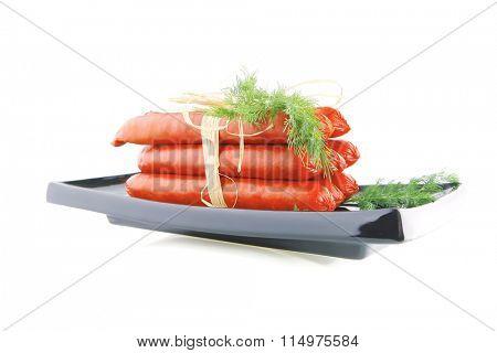 fresh pork smoked sausages on a black plate