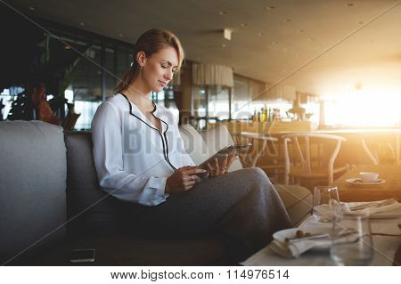 Elegant businesswoman chatting on touch pad while sitting in comfortable coffee shop