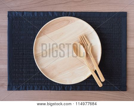 An Empty Wooden Plate With Wooden Spoons And Forks