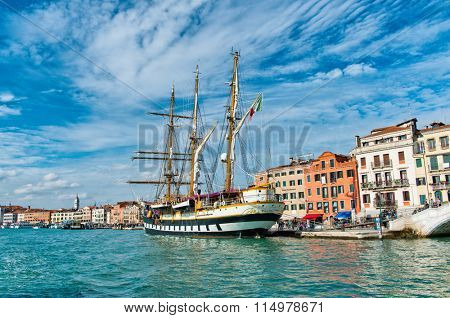 VENICE - AUGUST 27: View of the three masted barquentine, Palinuro, an Italian navy training ship, moored in front of historic buildings in the Giudecca Canal. August 27, 2015 in Venice.