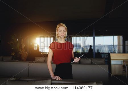Young female creative designer holding touch pad while standing in modern interior