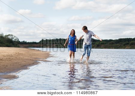 A Young Couple Walks Along The Beach.