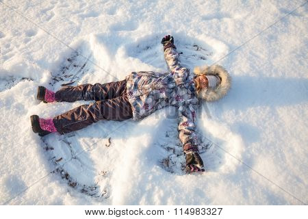 Happy girl wearing warm winter clothing having fun laying in a fresh snow making snow angels