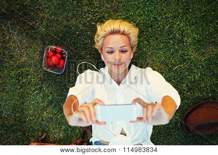 Charming blonde hair female taking picture with cell telephone during rest in a meadow