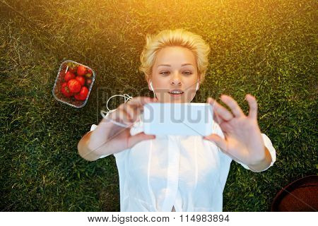 Attractive female student taking picture with cell telephone camera while lying on a lawn