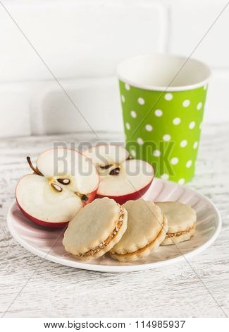 Cookies With Caramel Cream And Walnuts, Apple And A Glass Of Milk On White Wooden Background