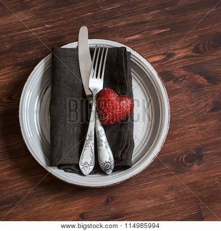 Romantic Table Setting - Plate, Knife, Fork, Napkin And A Red Heart, For Valentines Day. On A Dark W