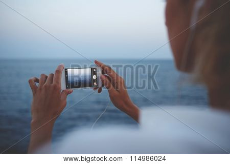 Woman taking picture on cell telephone camera while enjoying her weekend vacation overseas