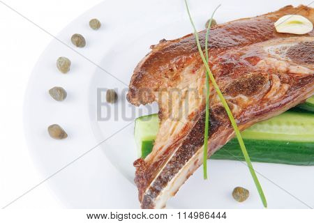 hot red beef meat steak on white plate with capers and tomatoes isolated over white background