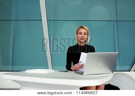 Confident businesswoman holding paper documents while sitting front of open net-book in office