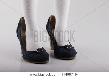 of the child's feet in large female shoes