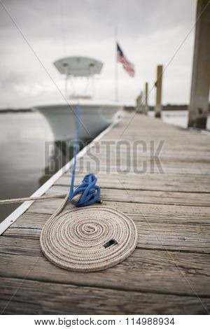 coil of rope leading to out of focus boat in background
