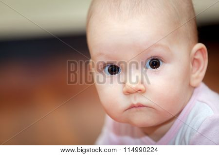 Close-up of a small child who cries but does not scream. A tear rolling down his cheek. Blurred back