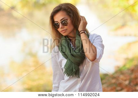 Sunny portrait of a beautiful young woman is sunglasses and in a green scarf