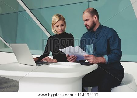 Man and woman professional team using laptop computer to work on a joint project