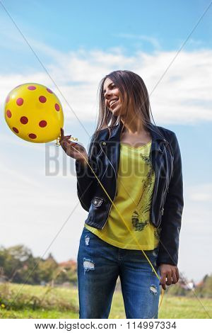 smiling young ordinary  woman in blue jeans and leather jacket  with balloon outdoors against sky